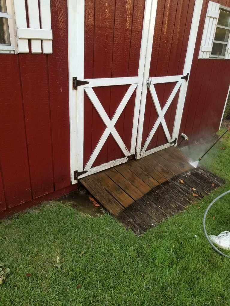 Power washing wood ramp of shed